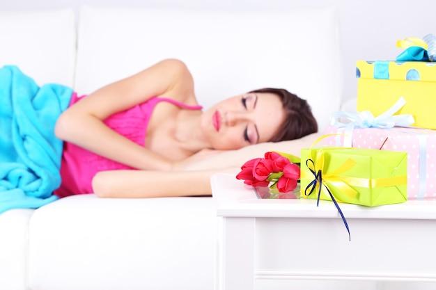 선물과 꽃이 있는 테이블 근처 소파에서 자고 있는 아름다운 젊은 여성, 클로즈업
