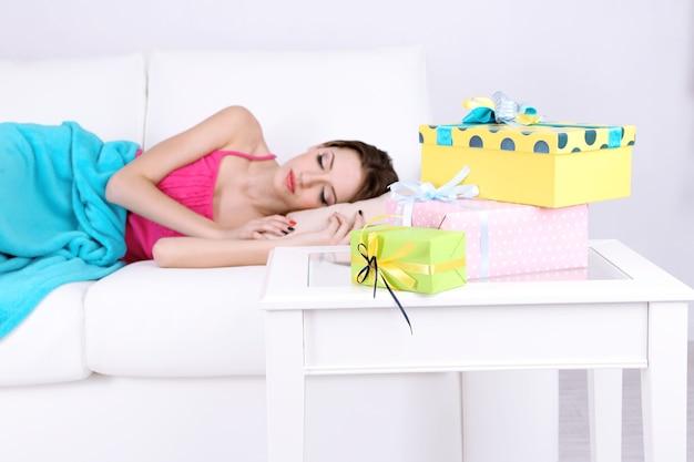 贈り物や花とテーブルの近くのソファで寝ている美しい若い女性、クローズアップ
