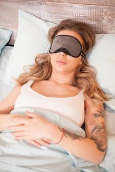 彼女の枕にカバーアイマスクで寝ている美しい若い女性。