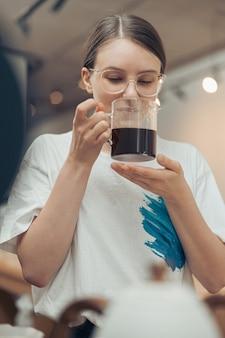 Красивая молодая женщина, пахнущая кофе в кафетерии