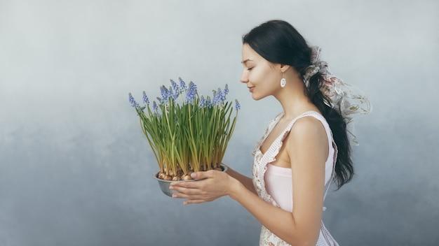 Красивая молодая женщина, пахнущая весенними цветами в цветочном горшке, чувственная романтическая женщина смешанной расы