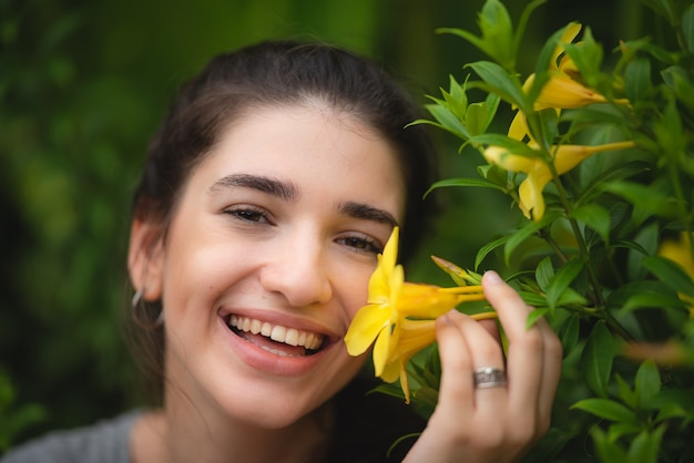 Beautiful young woman smelling yellow flower in the park, happy morning