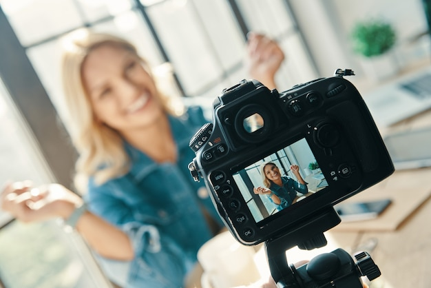 미소하고 디지털 카메라 앞에 앉아있는 동안 몸짓 아름다운 젊은 여자