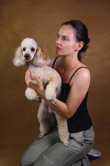 웃 고 화려한 난쟁이 흰색 푸들 강아지를 들고 아름 다운 젊은 여자. 그녀는 갈색 스튜디오 벽에 앉아 개를보고 있습니다.