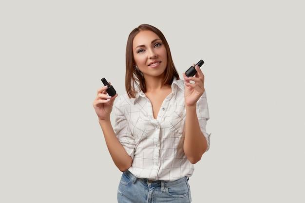 Красивая молодая женщина улыбается и смотрит в камеру, держа бутылки лака для ногтей портрет красоты ...