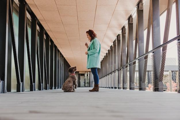 携帯電話を使用して、笑みを浮かべて、通路の真ん中に立っている美しい若い女性。屋内。彼女のかわいい茶色の犬の写真を撮る。