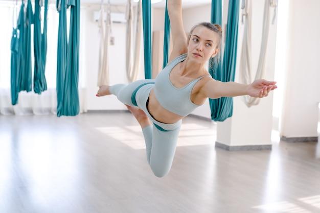 Красивая молодая женщина улыбается и использует гамак для выполнения позы антигравитационной йоги в студии йоги