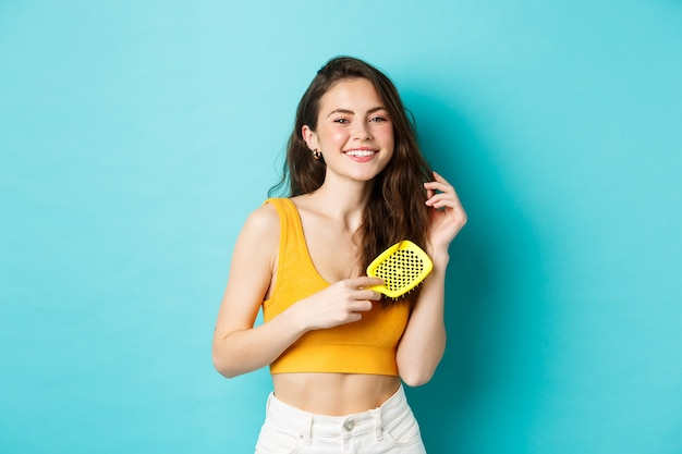 Beautiful young woman smiling, brushing healthy long hair with hairbrush, standing against blue background