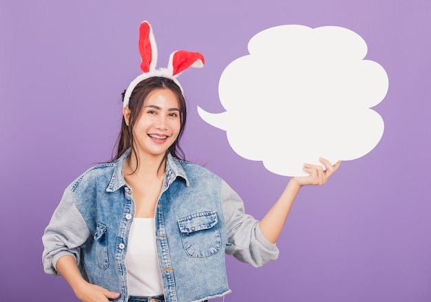 Beautiful young woman smiling excited wearing rabbit ears and denims holding empty speech bubble