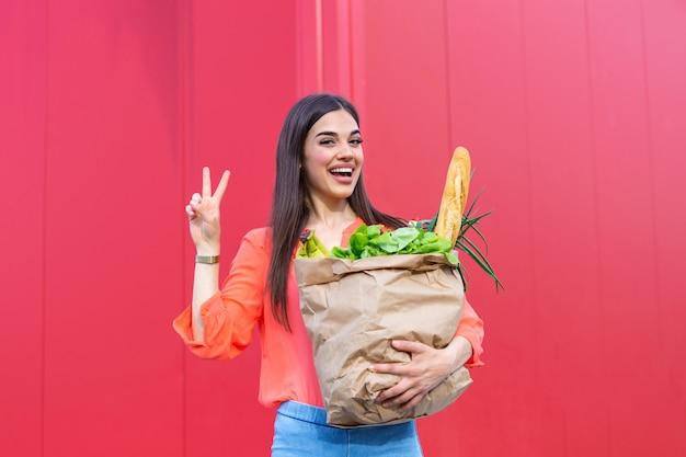食料品でいっぱい紙袋を持って笑っている美しい若い女性。赤い背景の上に食料品とバッグを持って幸せなかわいい女の子