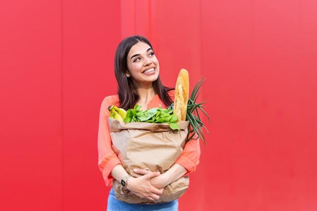 Красивая молодая женщина, улыбаясь, держа бумажный пакет с продуктами