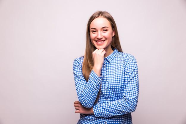 白い壁に孤立した笑顔の美しい若い女性