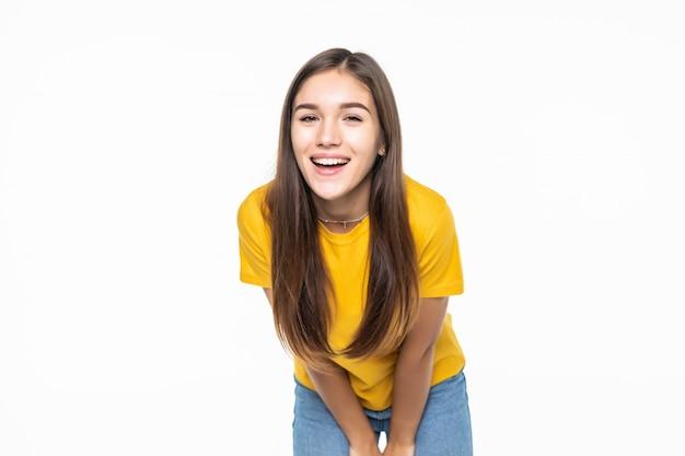 Красивая молодая женщина улыбается, пожалуйста, изолированные на белой стене