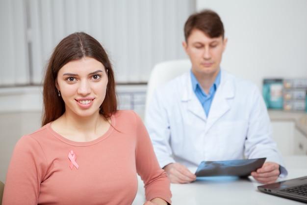 Красивая молодая женщина улыбается, носить символ осведомленности рака груди, розовую ленту на ее рубашке