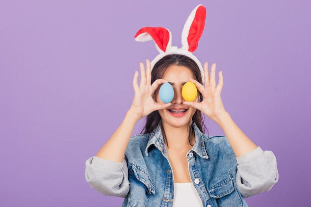 Beautiful young woman smiling wearing rabbit ears and denim holding colorful easter eggs front eyes