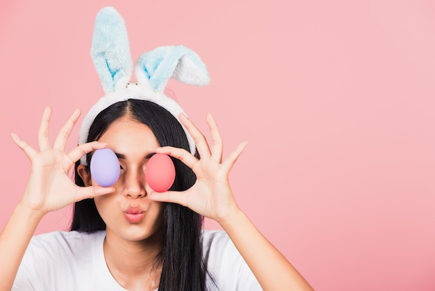 Beautiful young woman smiling wearing rabbit ears holding colorful easter eggs front eyes