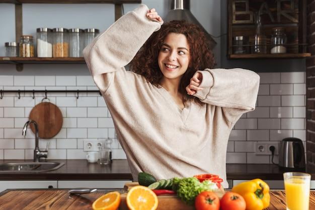Красивая молодая женщина улыбается во время приготовления салата из свежих овощей в интерьере кухни дома