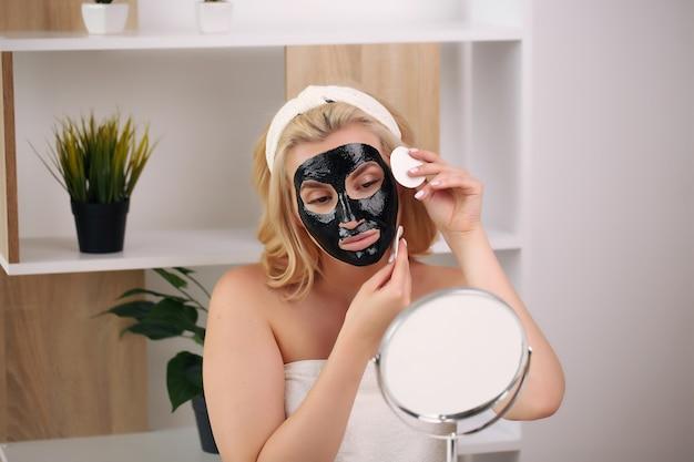 Красивая молодая женщина улыбается с банным полотенцем на ее теле и черной маской.