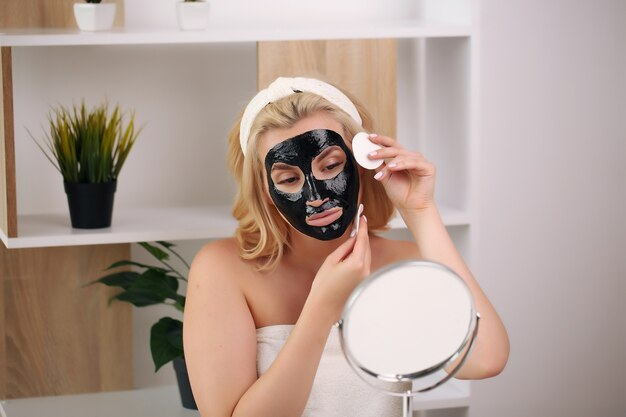 Beautiful young woman smiling with a bath towel on her body and a black mask.
