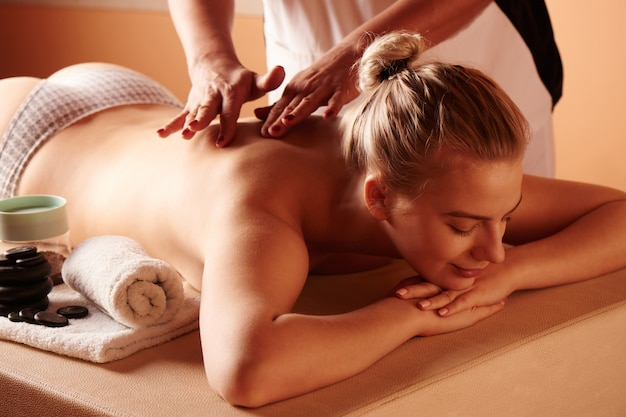 Beautiful young woman on a spa treatment receives massage from a professional female masseuse and enjoys the process