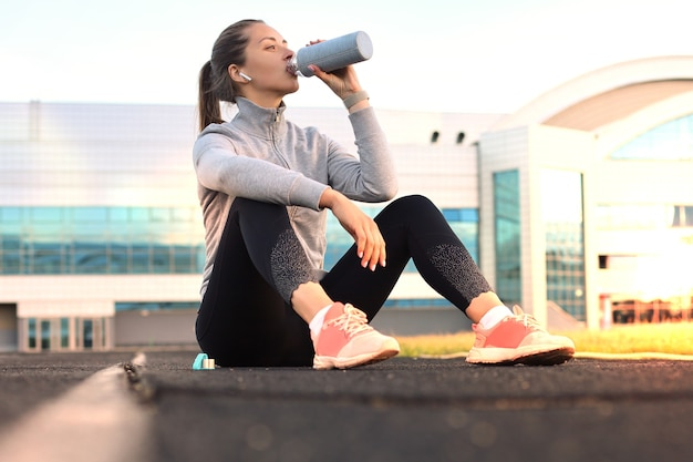 Beautiful young woman in sports clothing drinking water after sport exercise outdoors in stadium.