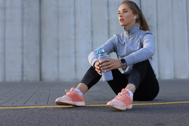 Beautiful young woman in sports clothing drinking water after sport exercise outdoors.