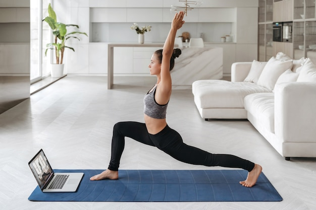 Beautiful young woman in sports clothing practicing yoga at home, watching online tutorial