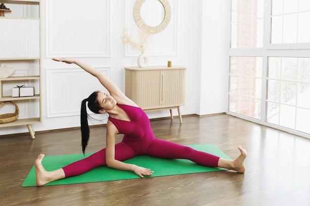 Beautiful young woman in sportswear practicing yoga on a gymnastic mat in the room doing the parivritta janu shirshasana exercise