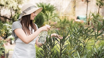 Beautiful young woman spraying water from bottle on growing plants
