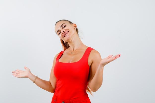 赤いタンクトップで横に手のひらを広げて陽気に見える美しい若い女性。正面図。