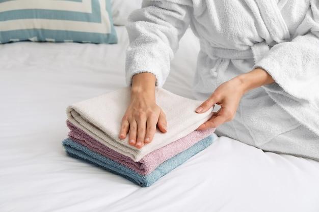 Красивая молодая женщина укладывает чистые полотенца на кровати