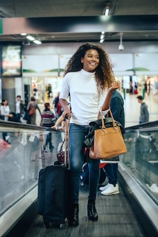Beautiful young woman at stairs with luggage.