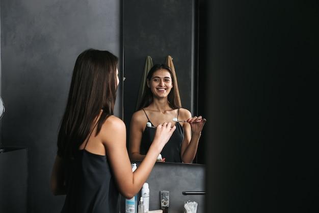 Красивая молодая женщина, стоя у зеркала в ванной по утрам