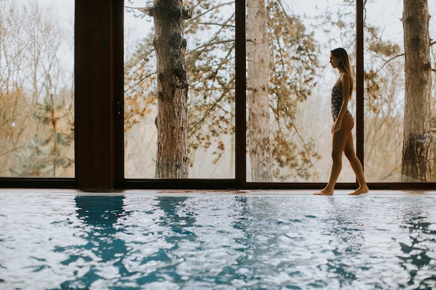 Beautiful young woman standing by the window at indoor swimming pool in spa