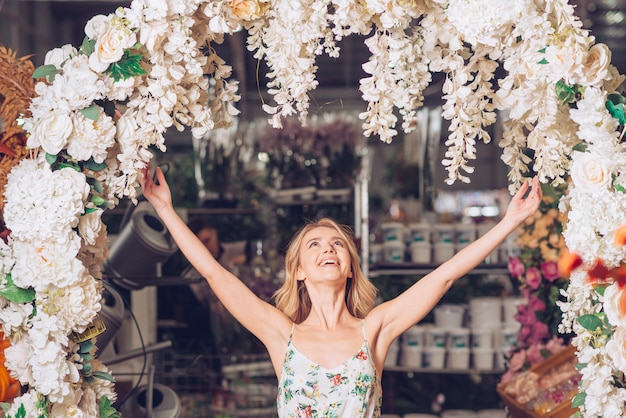 Beautiful young woman standing under the decorated curved entrance raising her arms and looking up
