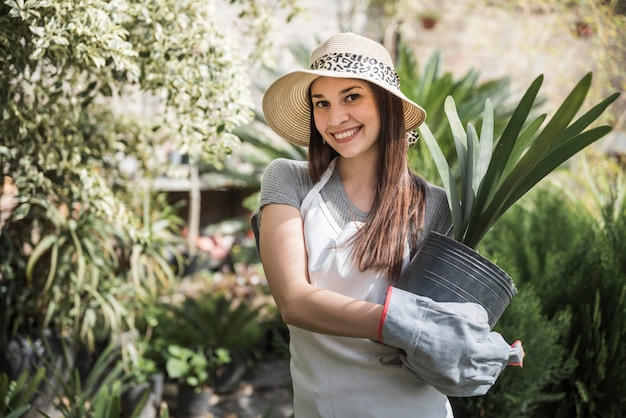 Beautiful young woman standing in the garden holding pot plant