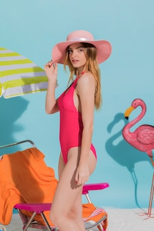Beautiful young woman standing in hat on beach in studio