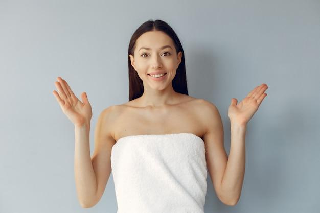 Красивая молодая женщина, стоя в полотенце