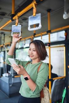 시내 버스에 서서 휴대전화를 보고 있는 아름다운 젊은 여성.