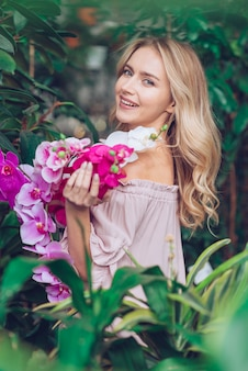 Beautiful young woman standing near the plants holding branches of orchid
