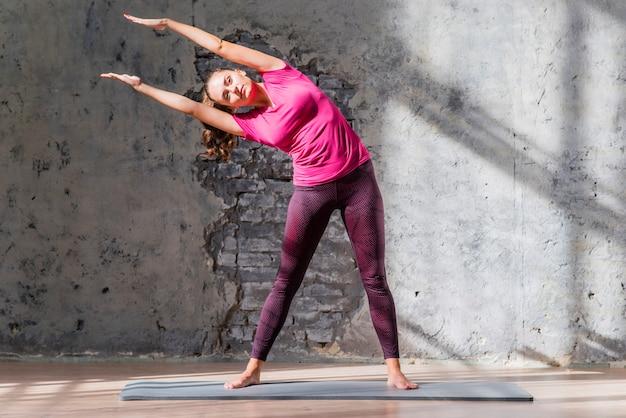 Красивая молодая женщина, стоя на тренировочный коврик, делая растяжку