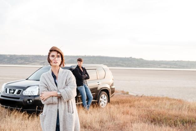 Красивая молодая женщина, стоя на окраине с мужчиной, опираясь на машину на заднем плане