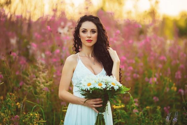 Красивая молодая женщина, стоя с букетом в руках, держа волосы