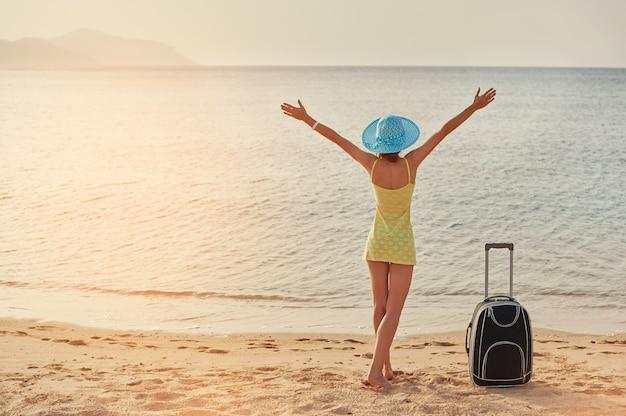 Красивая молодая женщина, стоя с чемоданом на прекрасном море, концепция времени путешествовать