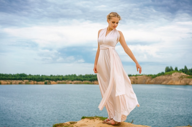 A beautiful young woman stands in a beautiful dress on a cliff