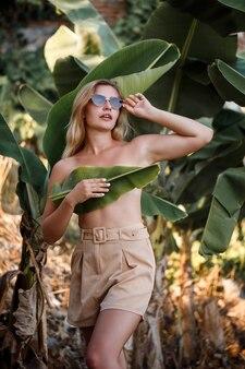 美しい若い女性がバナナの木の近くで美しいポーズで立って、バナナ農園でポートレート撮影