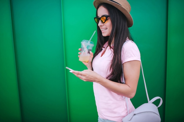Beautiful young woman stands and looks on the phone. she holds it in hands. also girl has cup of cold drink in another hand. she is smiling.