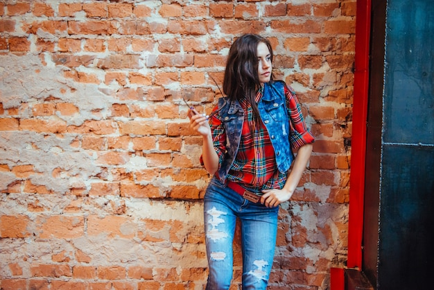 Beautiful young woman stands near the old brick wall.