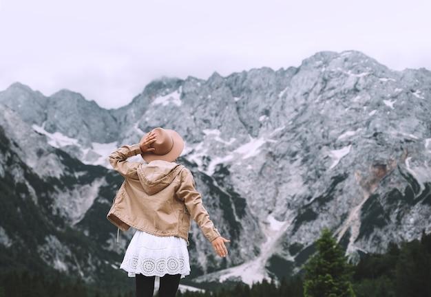 美しい若い女性が山の背景に立っています