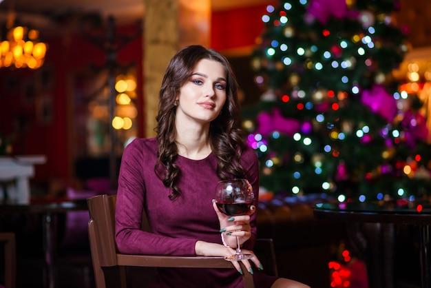 彼女の手でワイングラスを持つ美しい若い女性が立っています。